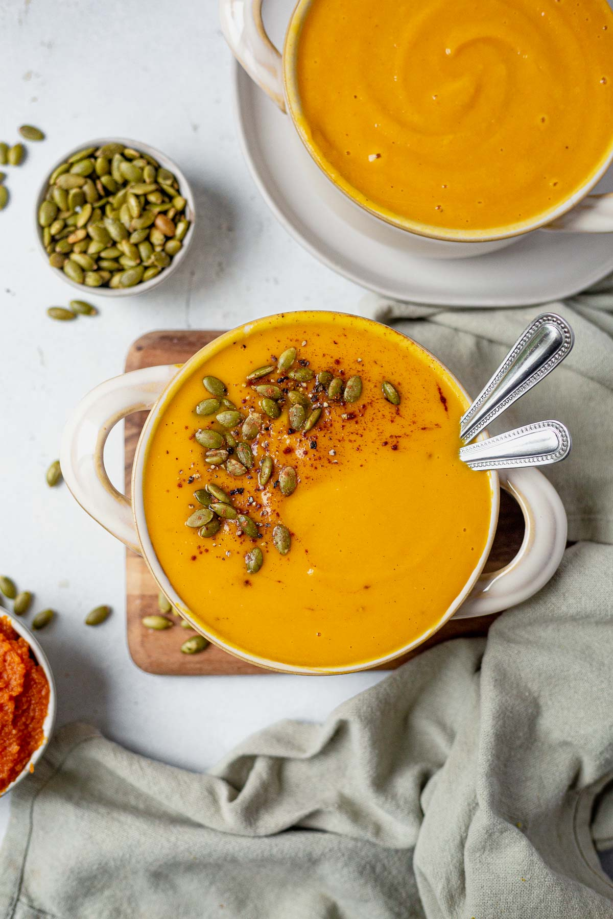 copycat panera bread autumn squash soup reipe in a soup bowl with two spoons